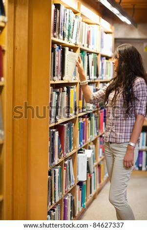 Portrait of a young woman choosing a book in a library - stock photo