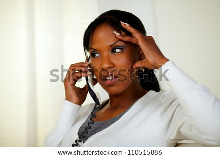 Portrait of a young woman conversing on phone with headache at home indoor