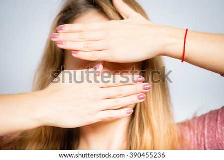 Portrait of a young woman covers her face with her hands, tired, isolated on a gray background - stock photo
