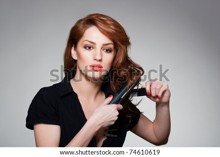 portrait of a young woman, curling her red hair with a flat iron