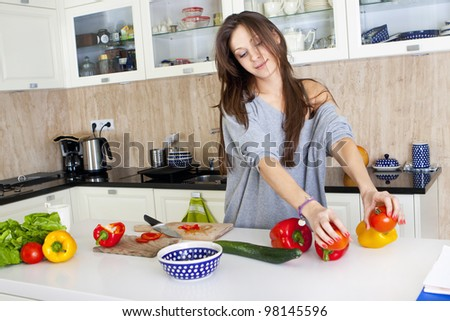 Portrait of a young woman doing a salad in her kitchen, while cooking, happy smile
