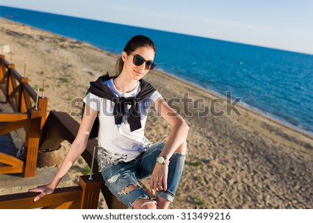 Portrait of a young woman dressed in stylish clothes and fashionable sunglasses sitting alone on the beach against of sea and sky background with copy space area for your text message or advertising - stock photo