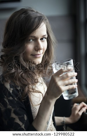 Portrait of a young woman drinking a pint glass of ice water. - stock photo
