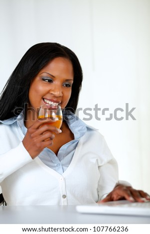 Portrait of a young woman drinking orange juice while looking to laptop screen - stock photo