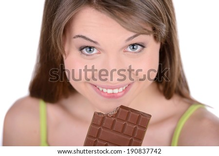 Portrait of a young woman eating a chocolate bar against a white background - stock photo