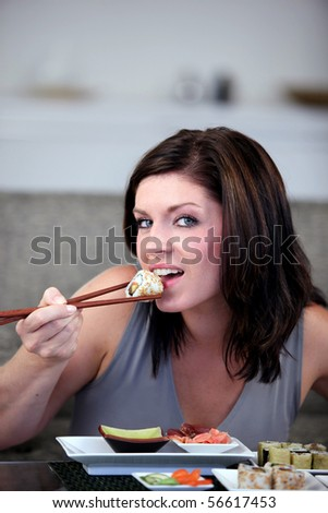 Portrait of a young woman eating a sushi with chopsticks