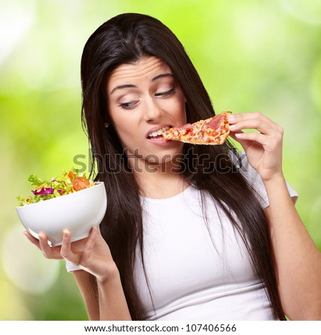 portrait of a young woman eating pizza and looking at a salad against a nature background