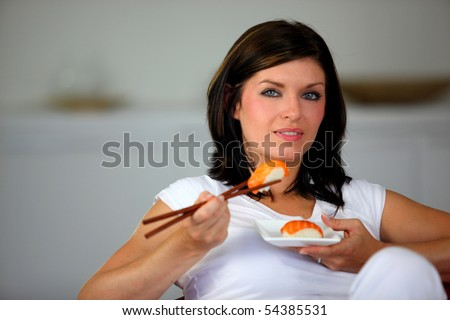Portrait of a young woman eating sushi with chopsticks