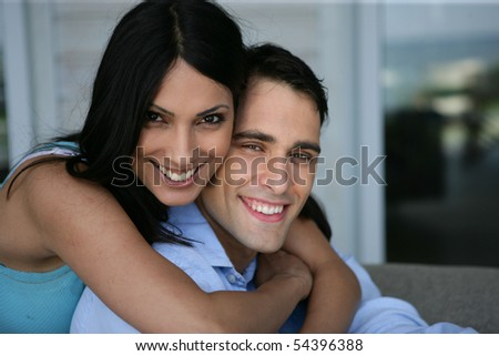 Portrait of a young woman embracing a smiling man - stock photo