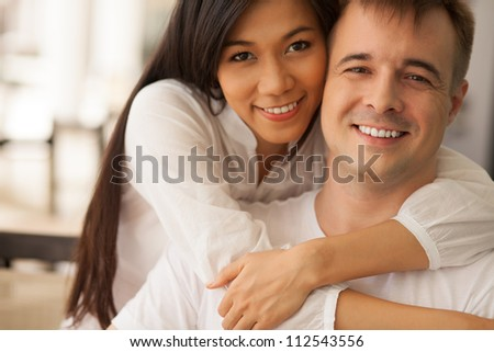 Portrait of a young woman embracing her boyfriend - stock photo