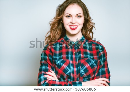 Portrait of a young woman folded her arms crosswise, isolated on a gray background - stock photo
