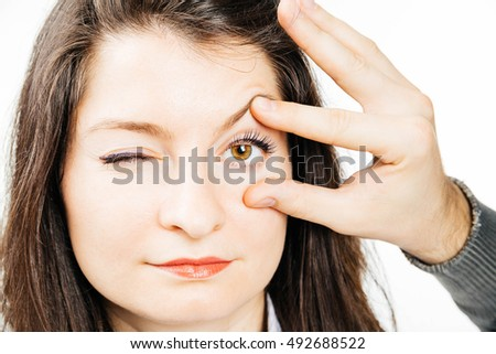 Portrait of a young woman having an eye examination - isolated on white.