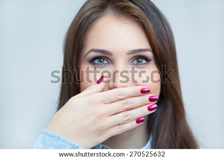 portrait of a young woman hiding her mouth with a hand - stock photo