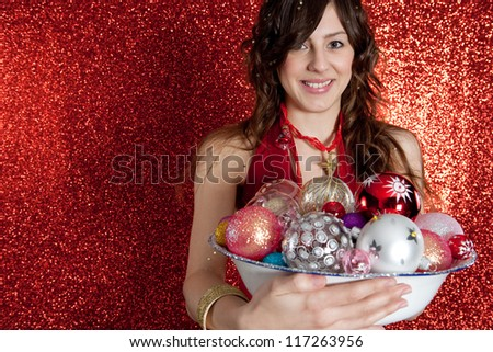 Portrait of a young woman holding a dish full of Christmas bar balls and smiling while standing in front of a red glitter background. - stock photo