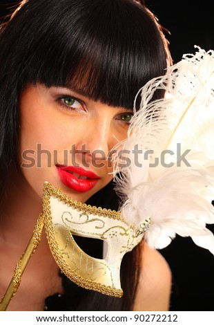 Portrait of a young woman holding a venetian mask - stock photo