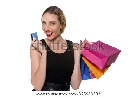 Portrait of a young woman holding colored shopping bags and credit card. Studio shot isolated on white.