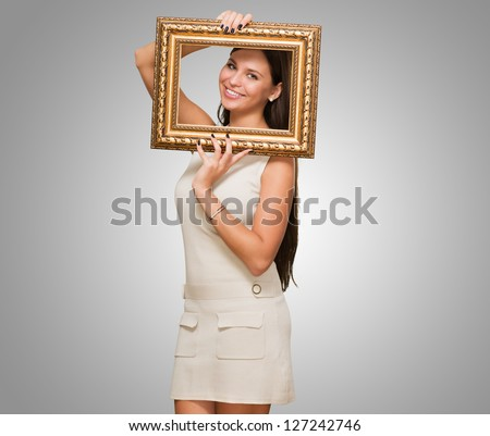Portrait Of A Young Woman Holding Frame against a grey background - stock photo