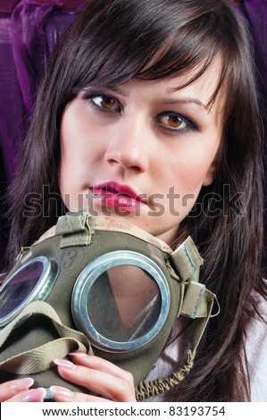 Portrait of a young woman holding her gas mask tight - stock photo