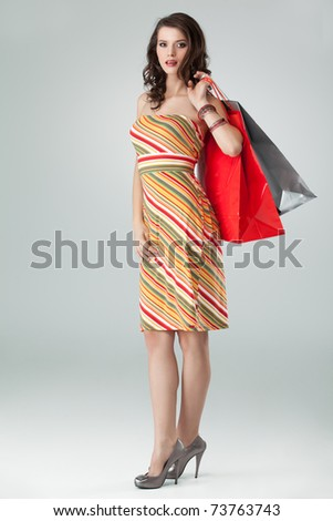 portrait of a young woman holding in one hand a few shopping bags and the other one on her hip. she is laughing and looking happy. - stock photo