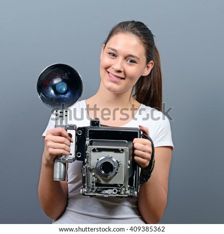 Portrait of a young woman holding retro camera against gray background