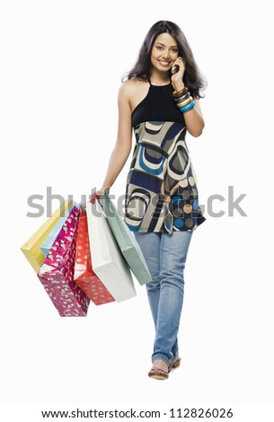 Portrait of a young woman holding shopping bags and talking on a mobile phone - stock photo