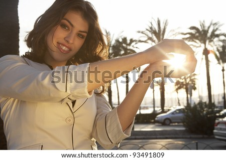 Portrait of a young woman holding the sun in her hands, with sun rays filtering through. - stock photo