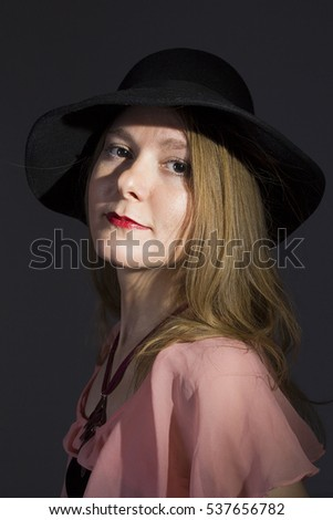 Portrait of a young woman in a hat on a black background