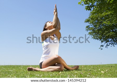 Portrait of a Young woman in a yoga Pose and Stretch outdoors - stock photo