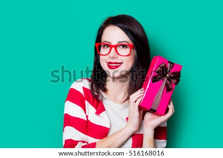 Portrait of a young woman in glasses with gift box on green background