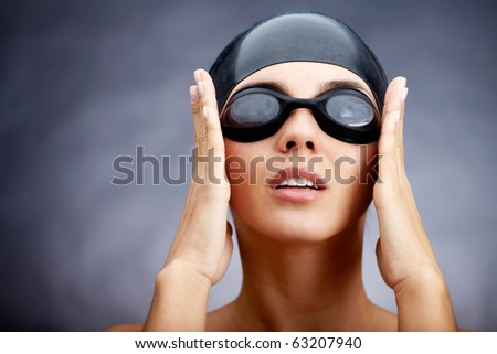 Portrait of a young woman in goggles and swimming cap - stock photo