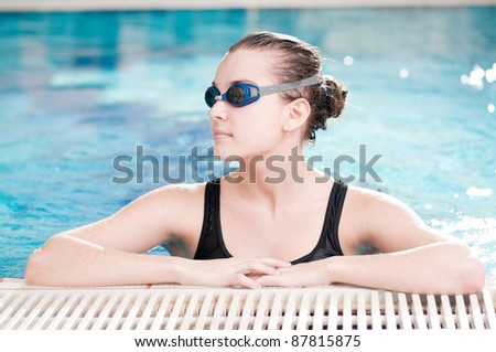 Portrait of a young woman in goggles in swimming pool - stock photo