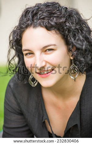 Portrait of a young woman in her mid twenties sitting outside on the lawn on a nice summer day, looking very happy, relaxed, self confident, and at piece. - stock photo