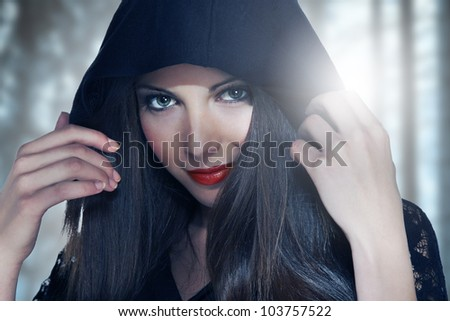 Portrait of a young woman in hood over forest background - stock photo