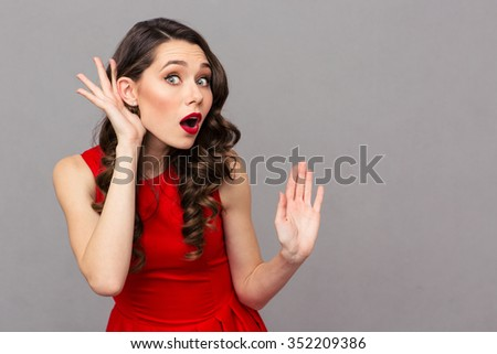 Portrait of a young woman in red dress listening what you got to say over gray background - stock photo
