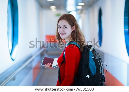 Portrait of a young woman in the boarding bridge, boarding an aircraft (color toned image) - stock photo