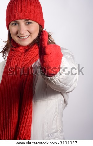 Portrait of a young woman in winter outerwear, doing a thumbs up. - stock photo
