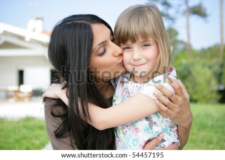 Portrait of a young woman kissing a little girl on the cheek - stock photo