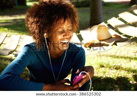 Portrait of a young woman laughing with mobile phone and earphones - stock photo