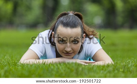 Portrait of a young woman laying in the grass in a park.