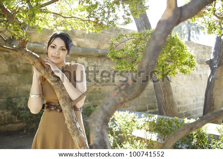 Portrait of a young woman leaning on a tree in a park, smiling at camera. - stock photo