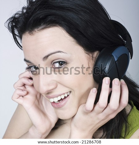 portrait of a young woman listening music on isolated background - stock photo