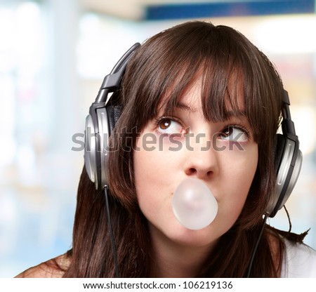 portrait of a young woman listening to music with bubble gum over an abstract background - stock photo