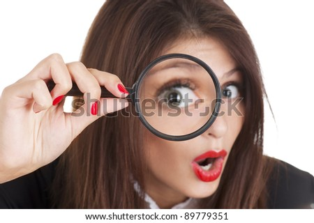 Portrait of a young woman looking at the camera through a magnifying glass with a surprised expression. Focus on the hand. - stock photo