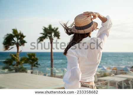 Portrait of a young woman looking at the sea, rear view - stock photo
