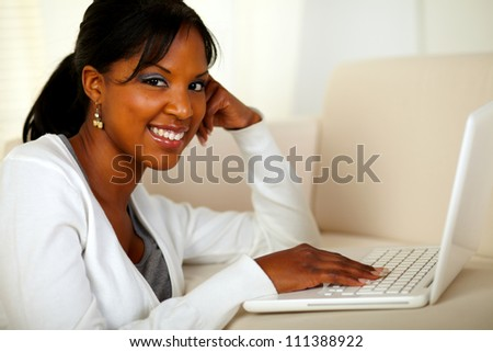 Portrait of a young woman looking at you while browsing the Internet at home indoor