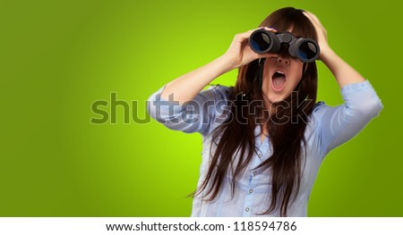 Portrait Of A Young Woman Looking Through Binoculars On Green Background