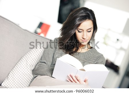 Portrait of a young woman lying on couch with book - stock photo
