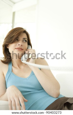 Portrait of a young woman making a phone call at home while sitting on a sofa.