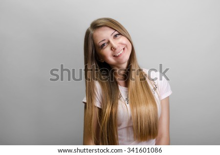 Portrait of a young woman on a gray background - stock photo