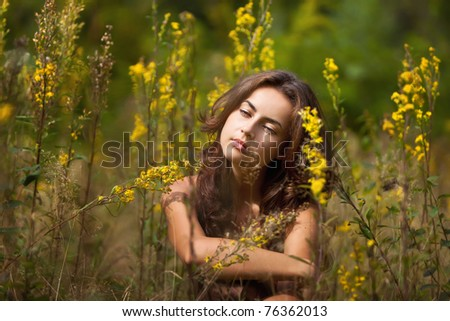 Portrait of a young woman on flowers field blured background - stock photo